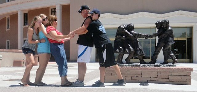 family imitating statue on road trip