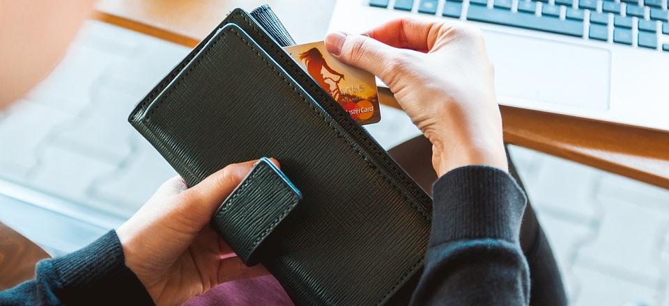 solo female traveller pulling credit card out of wallet