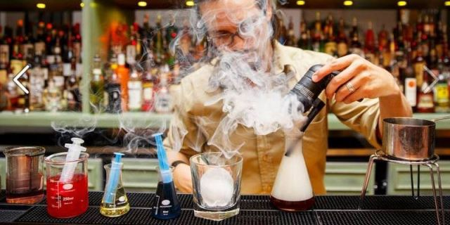 bartender at Alchemist Bar in London serving evening cocktails