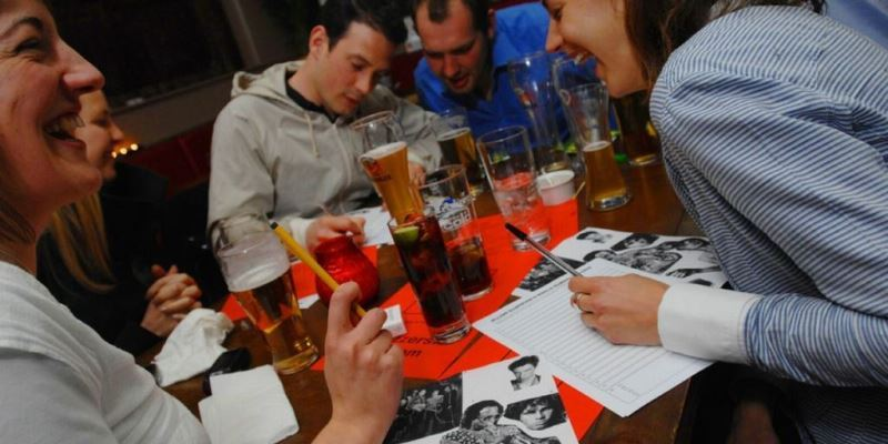 Group working on pub quiz in evening in London pub